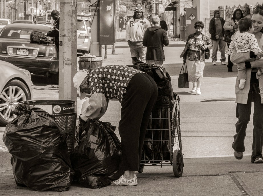 elderly woman searching trash bags for useable items