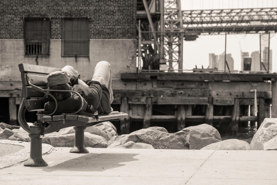 Man with cap sleeping on bench next to East river - Williamsburg