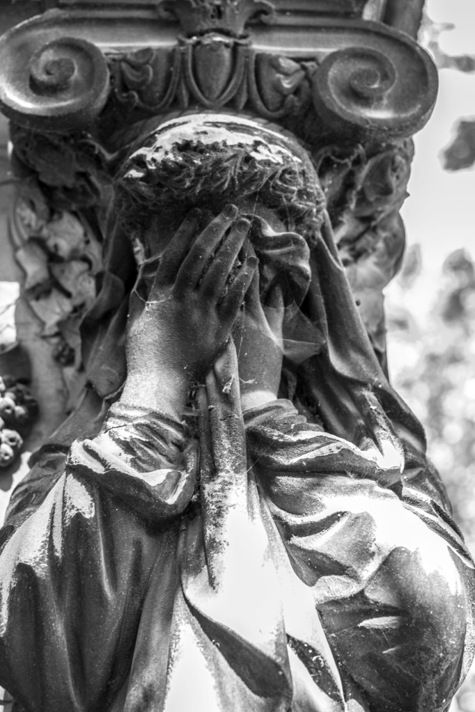 Photograph of female figure covering her face, weeping