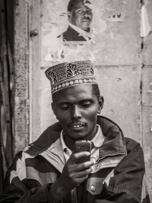 Photograph of Somali man looking at his cellphone with old poster from Kenyan elections on the wall behind him