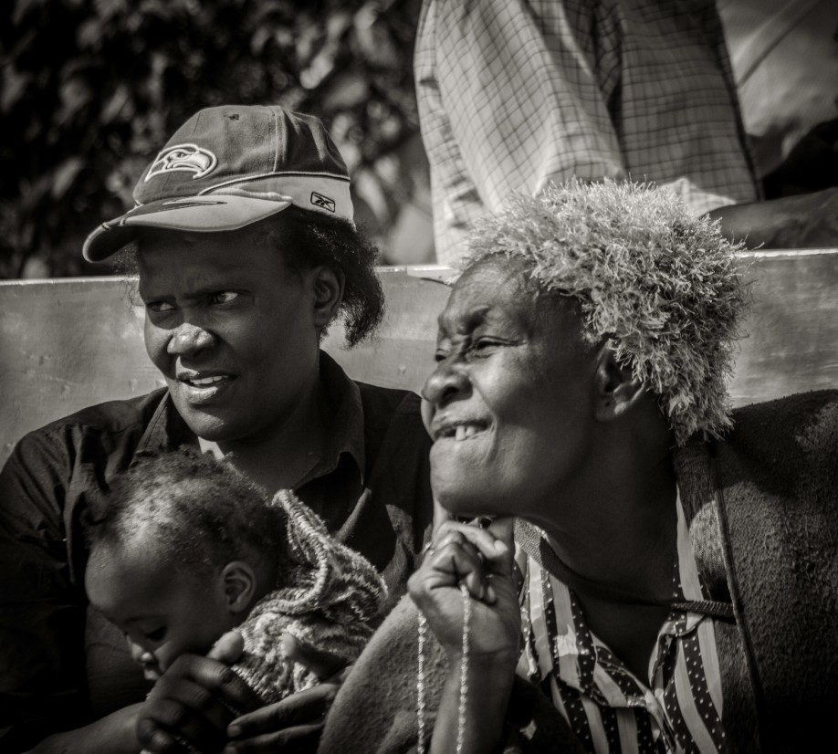 Two Kenyan ladies on a bench with baby, watching the passers-by I