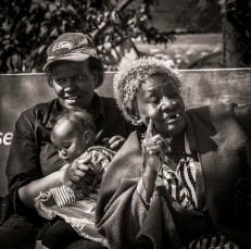 Two Kenyan ladies on a bench with baby, watching the passers-by II