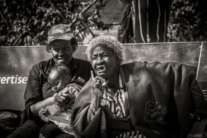 Two Kenyan ladies on a bench with baby, watching the passers-by IV