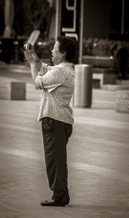Woman trying to take a picture of Burj Khalifa with point and shoot camera