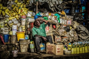 Photograph of market scene: man sitting in front of hundreds of containers and buckets for sale