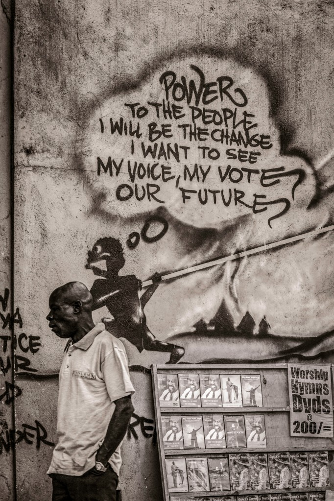 Photograph of Kenyan man walking by a wall graffiti saying 'Power to the People'