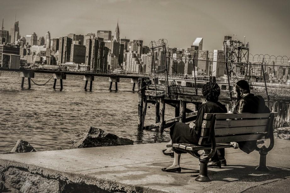 Photograph of Orthodox Jewish Williamburg couple sitting on bench looking at Manhattan