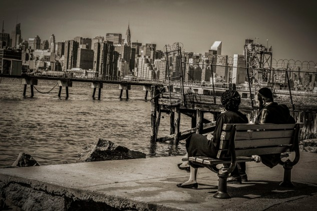 Photograph of Orthodox Jewish Williamburg couple sitting on bench looking at Manhattan