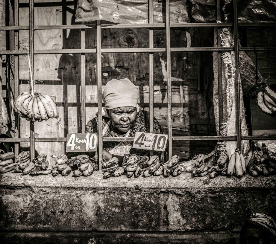 Photograph of elderly lady selling bananas