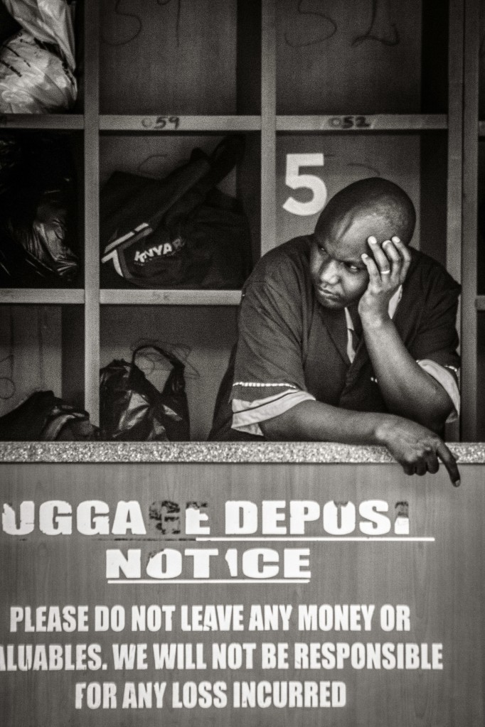 Photograph of seemingly bored employee at luggage deposit in Nairobi