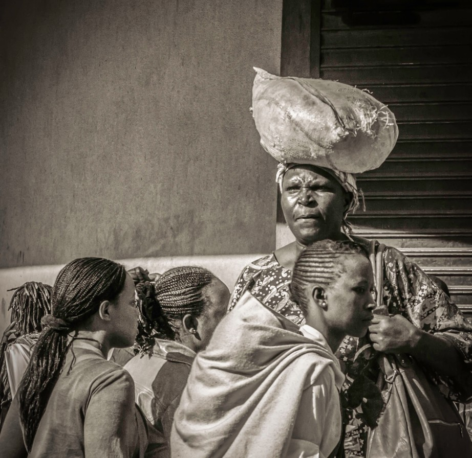 Photograph of rural woman in Nairobi, carrying a sack on her head