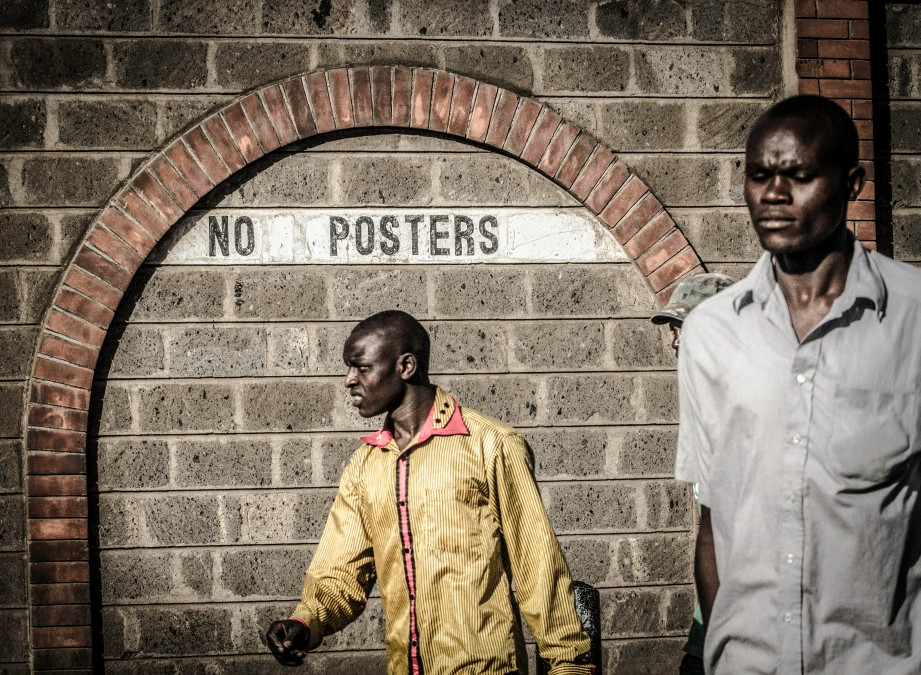 Photograph of two men passing by a wall with 'No Posters' written on it