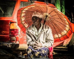 Photograph of elderly Kenyan woman with red umbrella