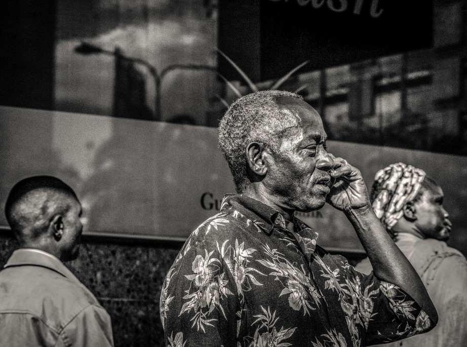 Photography of old men with mobile phone - passers by in the background