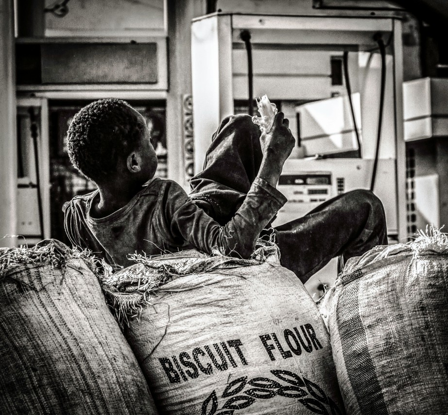 Monochrome photograph of Kenyan boy lying on bags of biscuit flour