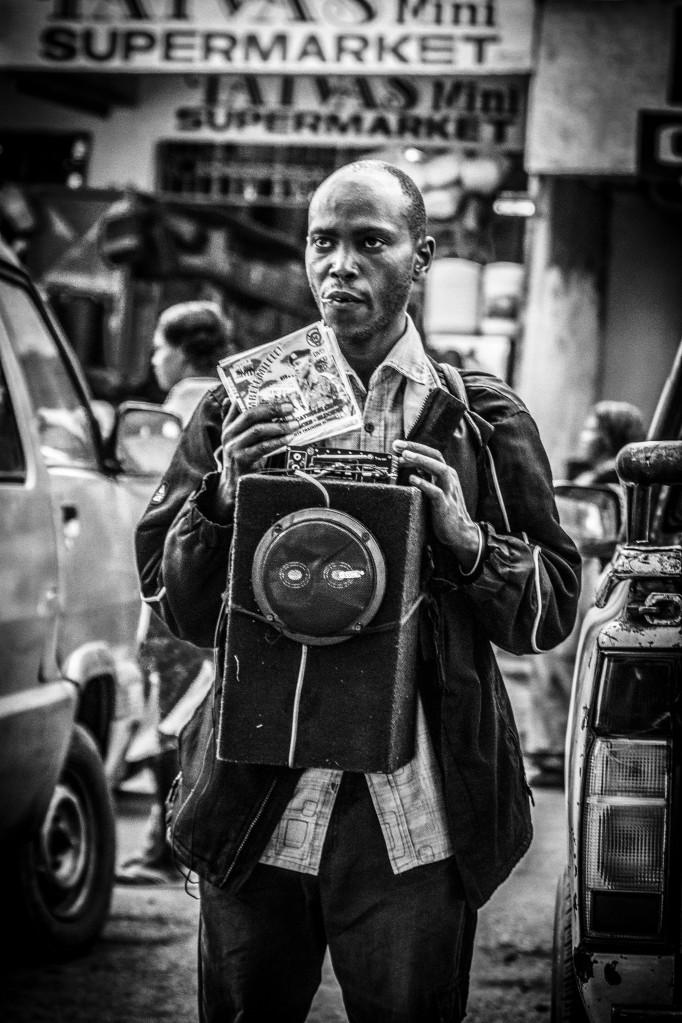 Photograph of street vendor in Limuru selling patriotic songs