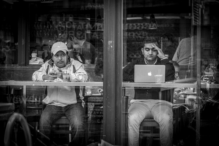 Two men siting in a coffeshop looking out of window - both online