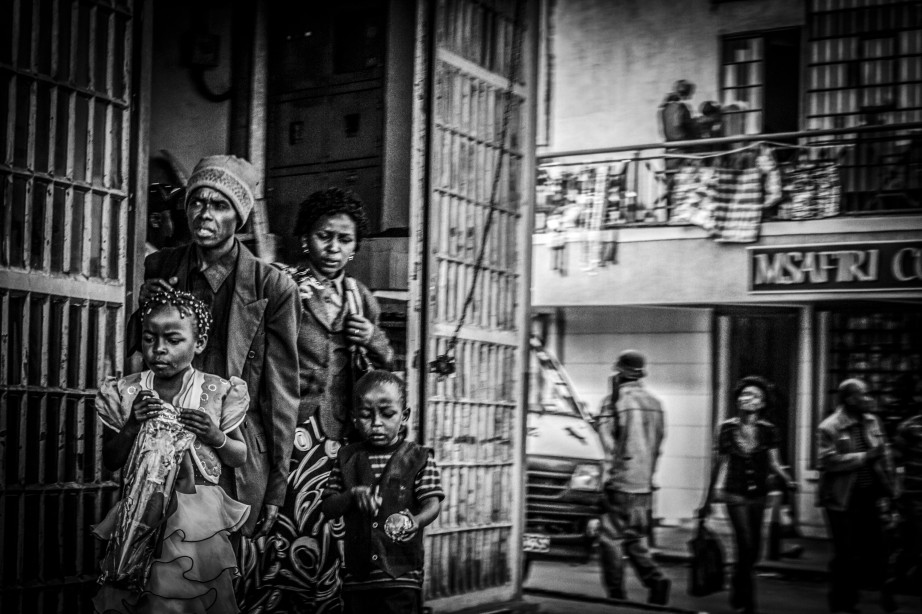 Monochrome photograph of family coming out of a downtown shop