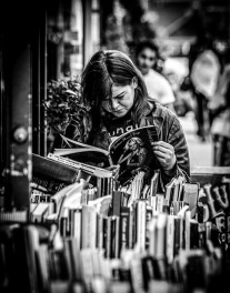 Monochrome photograph of girl in a bookstore, reading tattoo magazine