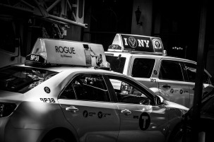 Monochrome street shot of two yellow cabs with ads