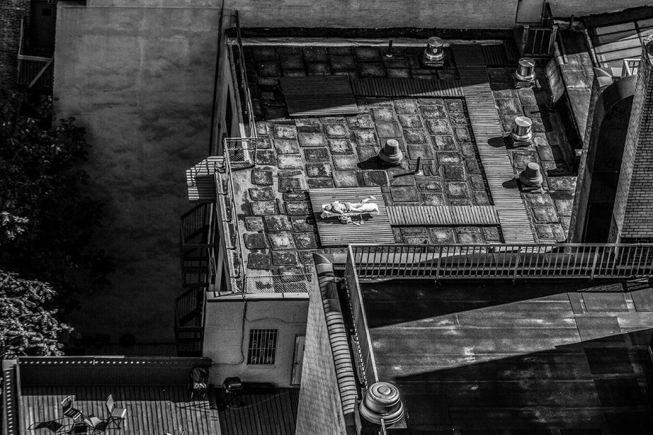 Monochrome - woman sunbathing on roof