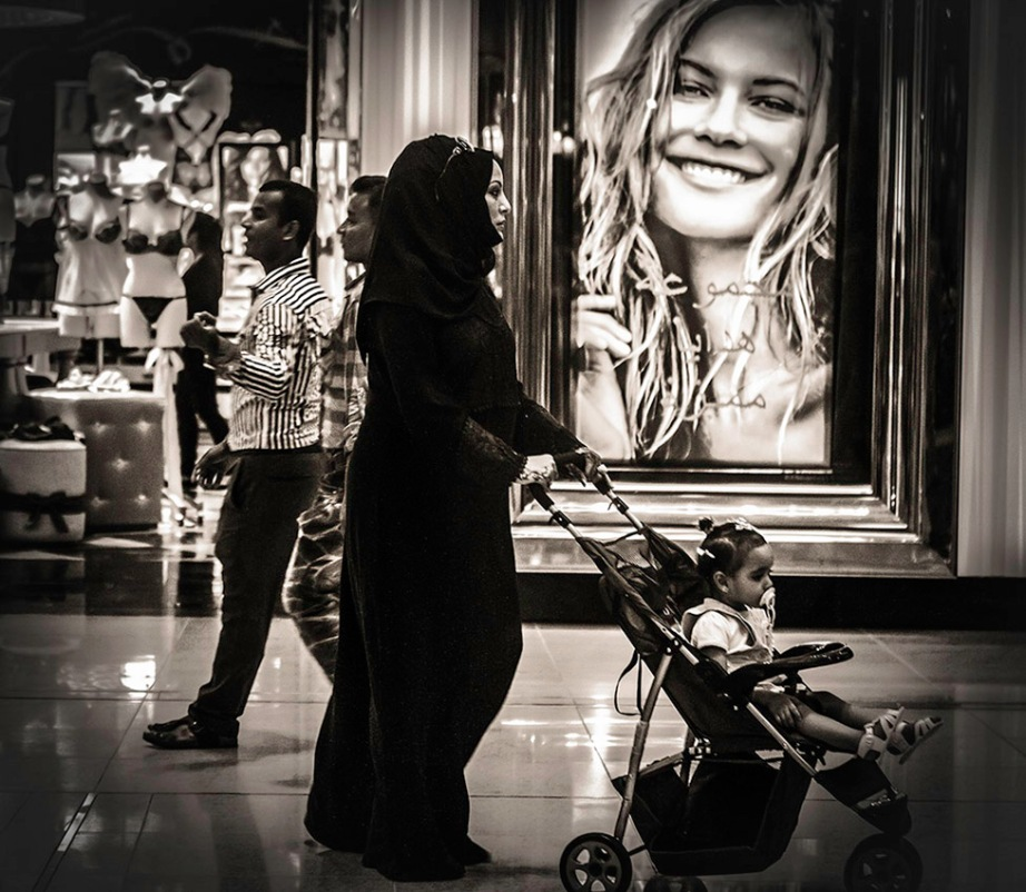 B&W Shot of Veiled Emirati Woman Passing by Victoria's Secret