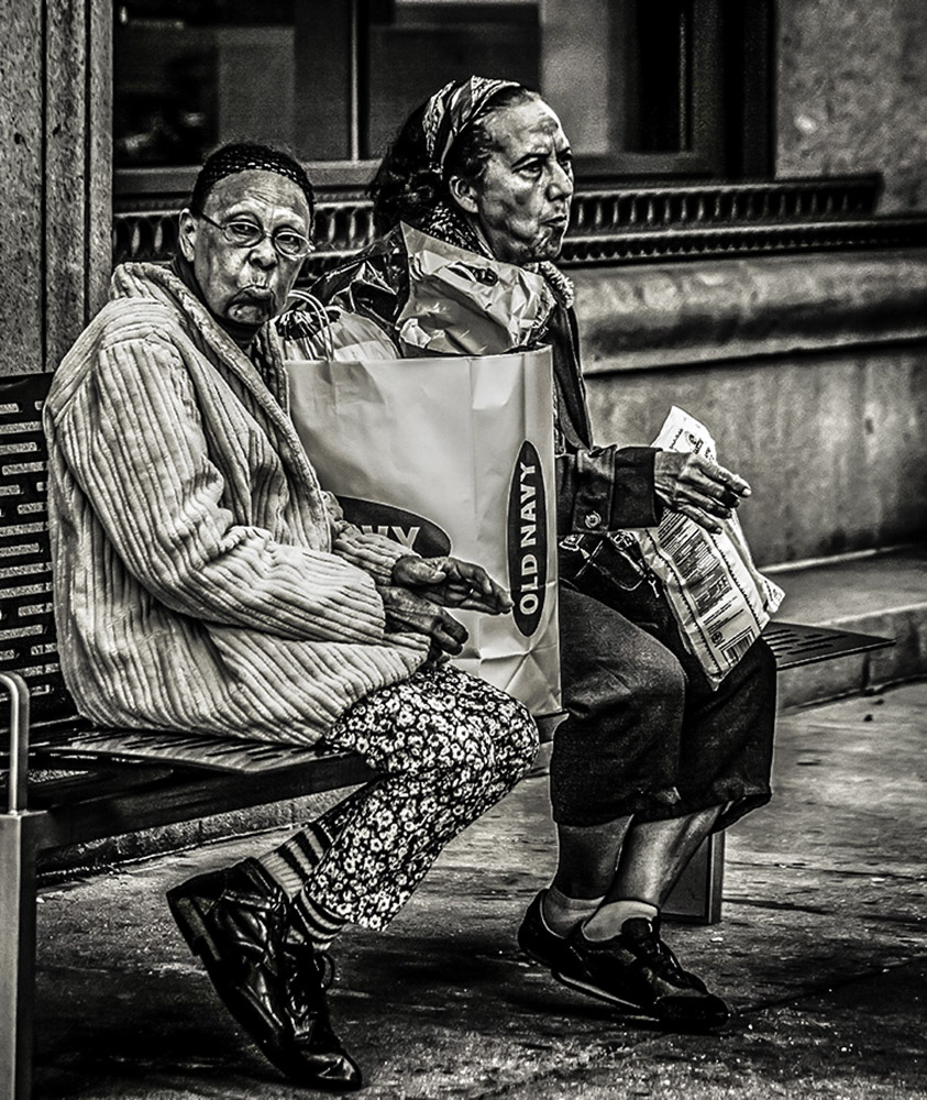Monochrome photograph of two elderly ladies on a bench