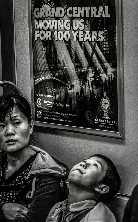 Monochrome snapshot of mother and son in front of poster 'Grand Central - Moving us for 100 Years'