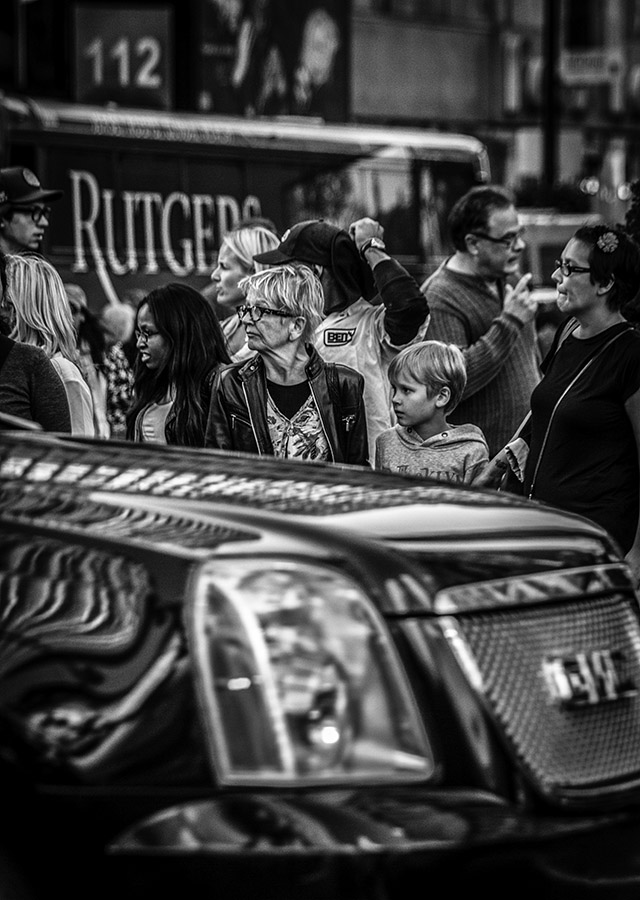 B&W Street Shot: people sandwiched between SUV and bus