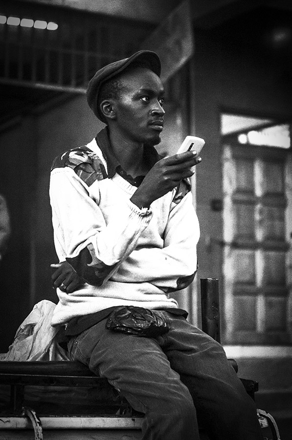 B&W photography of youngish Kenyan man with cellphone, looking distracted