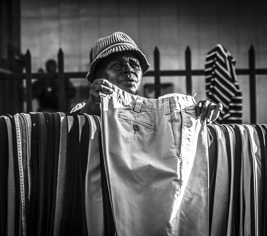 Monochrome photograph of man selling pants - Nbo
