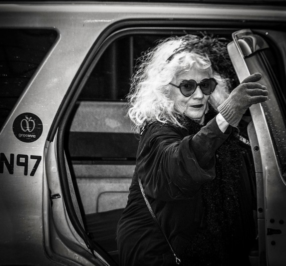 B&W snapshot of old lady with heart-shaped sunglasses arriving in Yellow cab