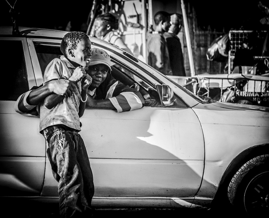 Monochrome street shot of man in a car + boy
