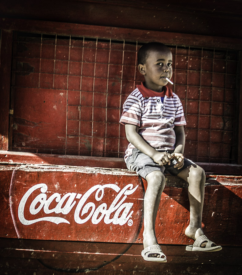 Colour shot of boy sitting on Coke stand