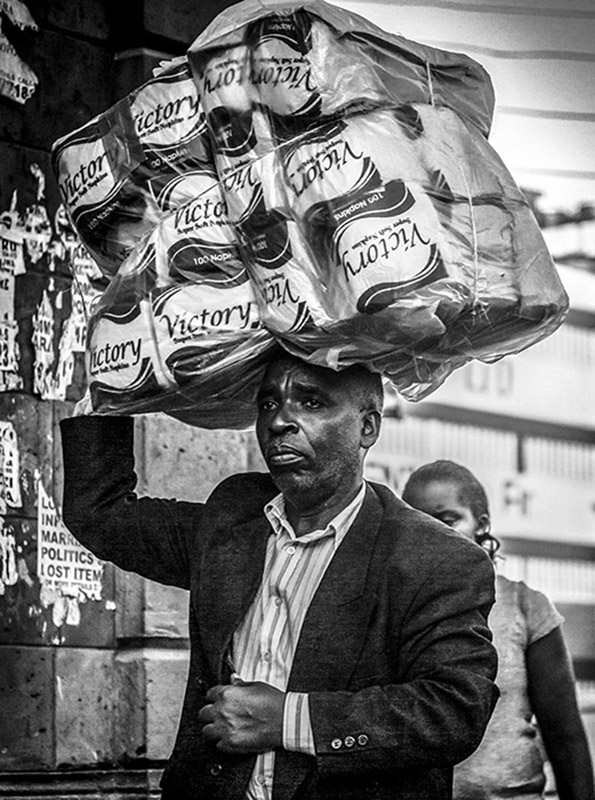 B&W photograph of Kenyan man carrying a bag of victory toilet paper on his head